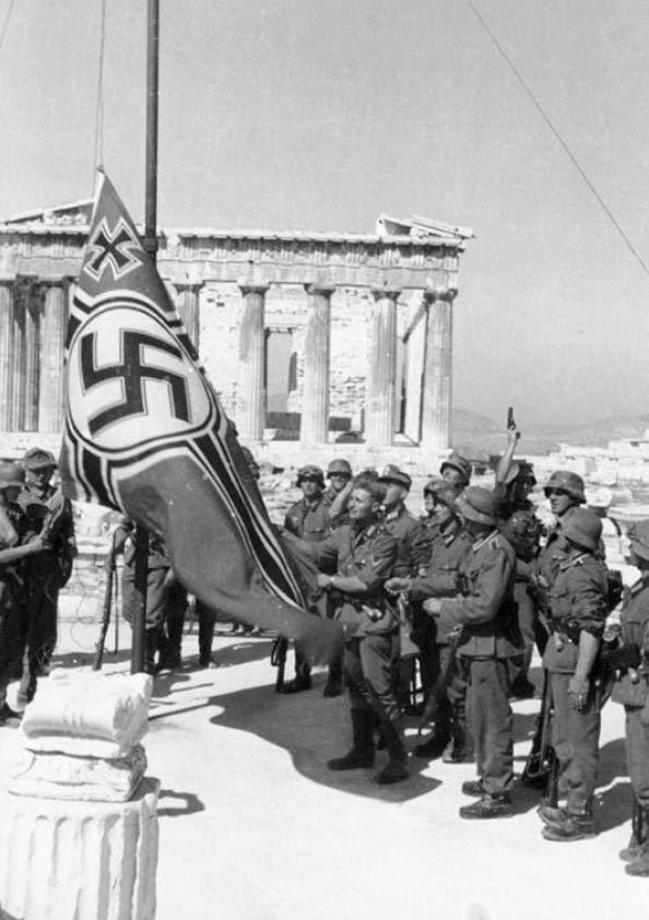 Апостолос Сантас у сорванного с Акрополя фашистского знамени со свастикой. Если флаг Победы над фашистским рейхстагом водрузили советские солдаты, то первыми в оккупированных европейских столицах сорвали фашистский флаг греки 31 мая 1941 г.