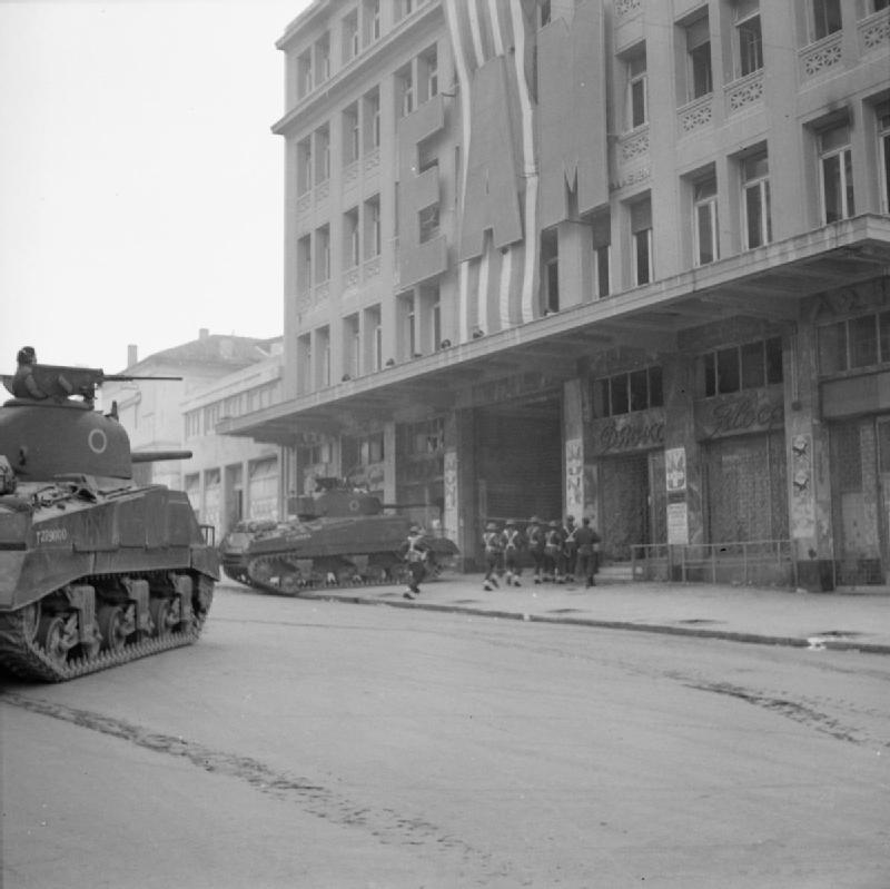 Британские танки и пехота врываются в здание афинского правления ЭАМ, по улице Кораи, в центре города. Фотография NA 20518 из коллекции ImperialWarMuseums.