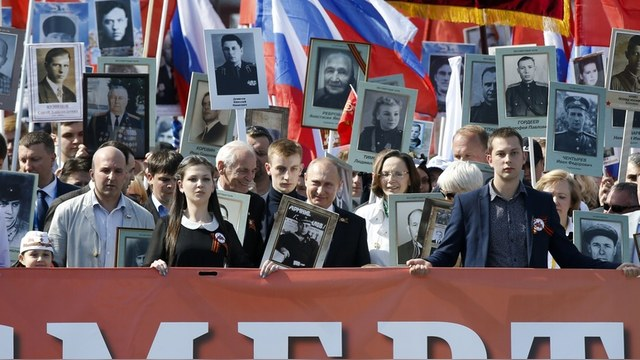 Russian President Vladimir Putin (C) holds the portrait of his father, war veteran Vladimir Spiridonovich Putin as he takes part in the Immortal Regiment march with pictures of World War Two soldiers on Red Square during the Victory Day celebrations in Moscow, Russia, May 9, 2015. Russia marks the 70th anniversary of the end of World War Two in Europe on Saturday with a military parade, showcasing new military hardware at a time when relations with the West have hit lows not seen since the Cold War.   REUTERS/Sergei Karpukhin   - RTX1C8GA
